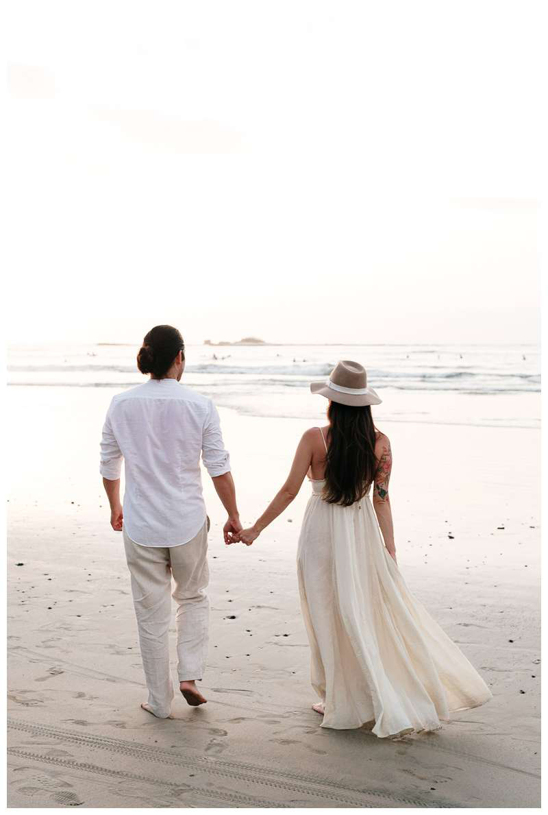 Pregnant woman and her husband walking on the beach in Tamarindo Costa Rica. Babymoon in Costa Rica maternity photos. Photographed by Kristen M. Brown of Samba to the Sea.