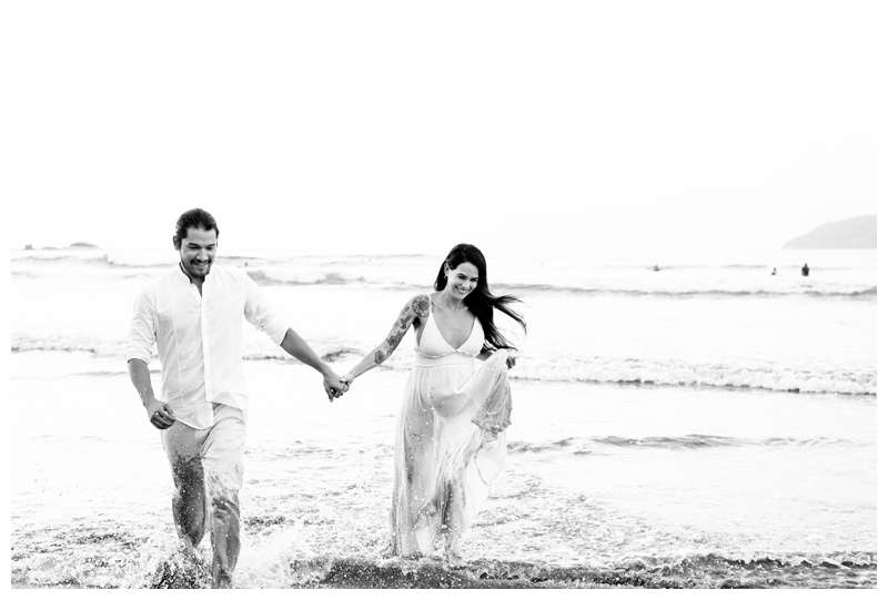 Pregnant woman and her husband running out of the ocean in Tamarindo Costa Rica. Babymoon in Costa Rica maternity photos. Photographed by Kristen M. Brown of Samba to the Sea.