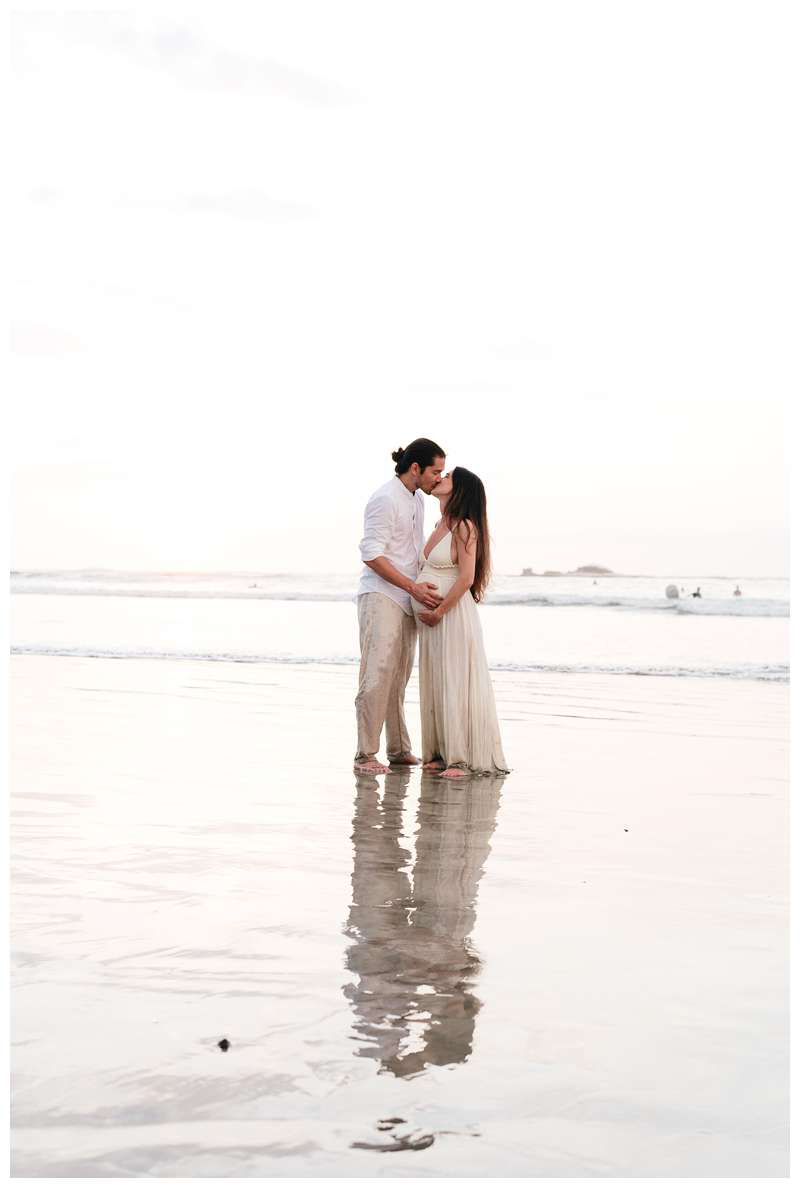 Pregnant woman and her husband kissing on the beach in Tamarindo Costa Rica. Babymoon in Costa Rica maternity photos. Photographed by Kristen M. Brown of Samba to the Sea.