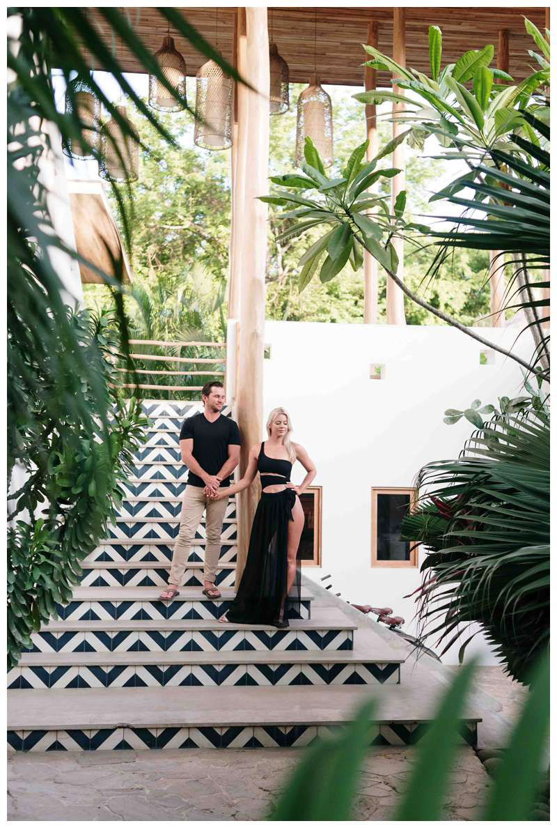 Couple standing on the stairs at The Nomadic hotel in Nosara. Engagement photos on the beach in Playa Guiones Nosara Costa Rica. Photographed by Kristen M. Brown of Samba to the Sea.