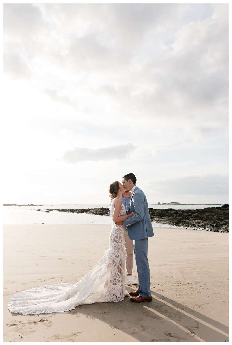 Bride and groom kissing during their minimony in Costa Rica on the beach in Tamarindo.  Photographed by Kristen M. Brown of Samba to the Sea.