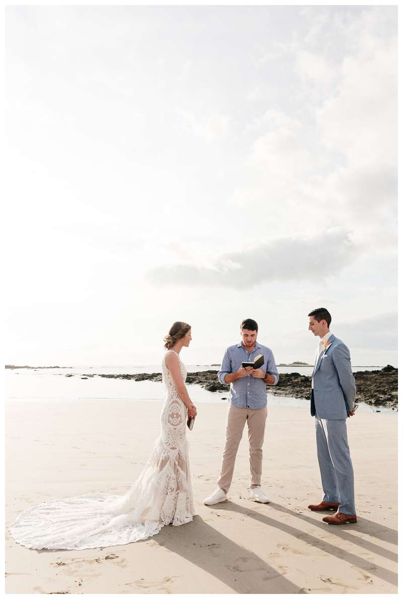 Bride and groom exchanging vows during their minimony in Costa Rica on the beach in Tamarindo.  Photographed by Kristen M. Brown of Samba to the Sea.