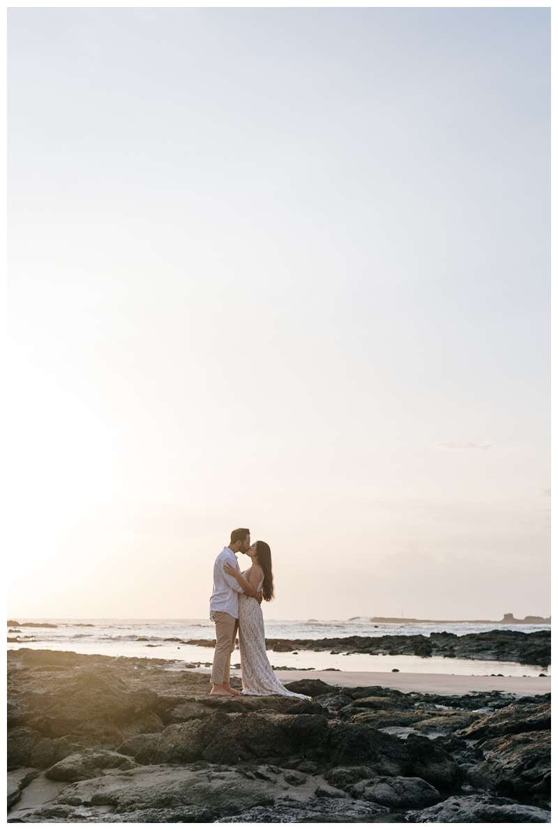 Husband and wife kissing on the beach during their anniversary photos in Costa Rica. Photographed by Kristen M. Brown of Samba to the Sea Photography.