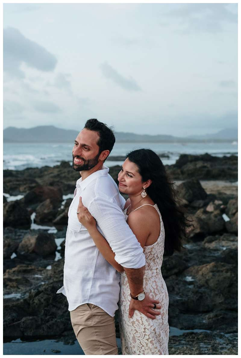 Husband and wife embracing on the beach during their anniversary photos in Costa Rica. Photographed by Kristen M. Brown of Samba to the Sea Photography.
