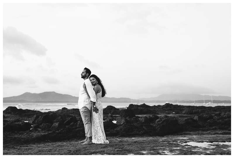 Black and white photo of husband and wife embracing on the beach during their anniversary photos in Costa Rica. Photographed by Kristen M. Brown of Samba to the Sea Photography.