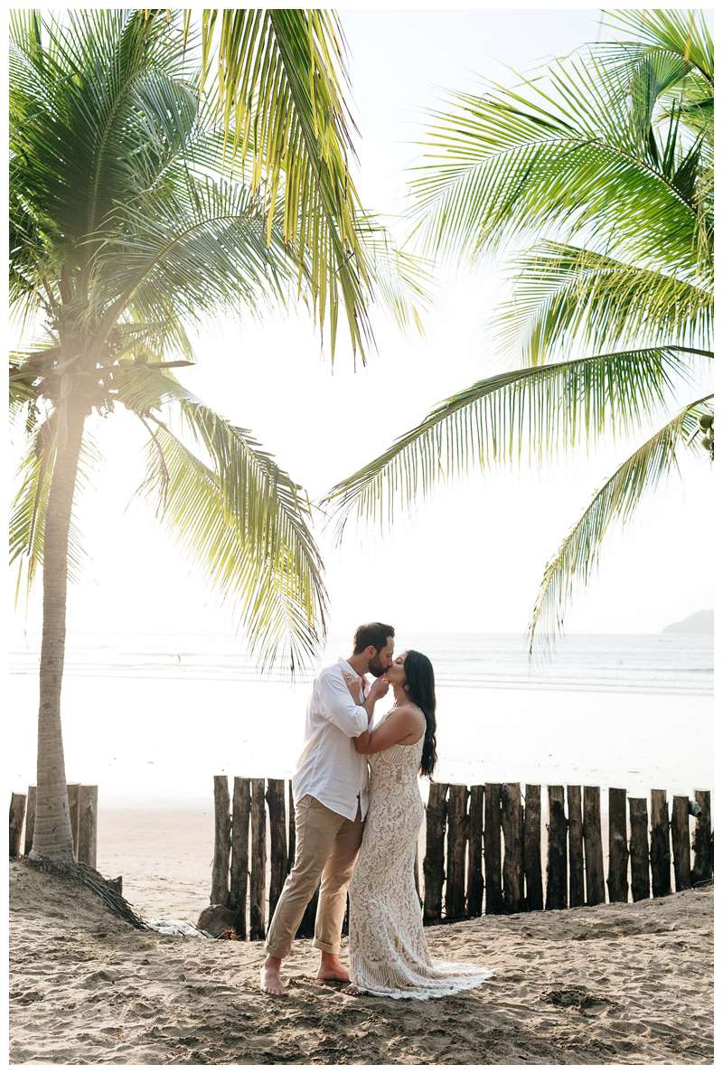 Husband and wife kissing under palm trees during their anniversary photos in Costa Rica. Photographed by Kristen M. Brown of Samba to the Sea Photography.