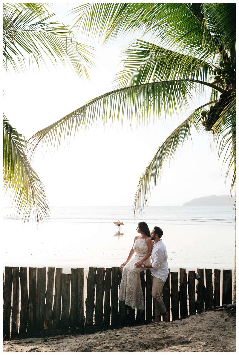 Husband and wife under palm trees during their anniversary photos in Costa Rica. Photographed by Kristen M. Brown of Samba to the Sea Photography.