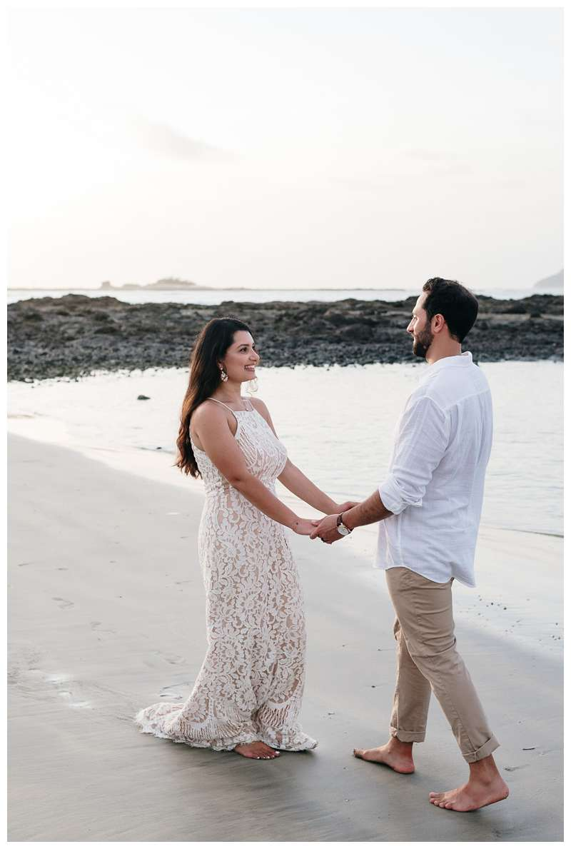 Husband and wife walking on the beach during their anniversary photos in Costa Rica. Photographed by Kristen M. Brown of Samba to the Sea Photography.