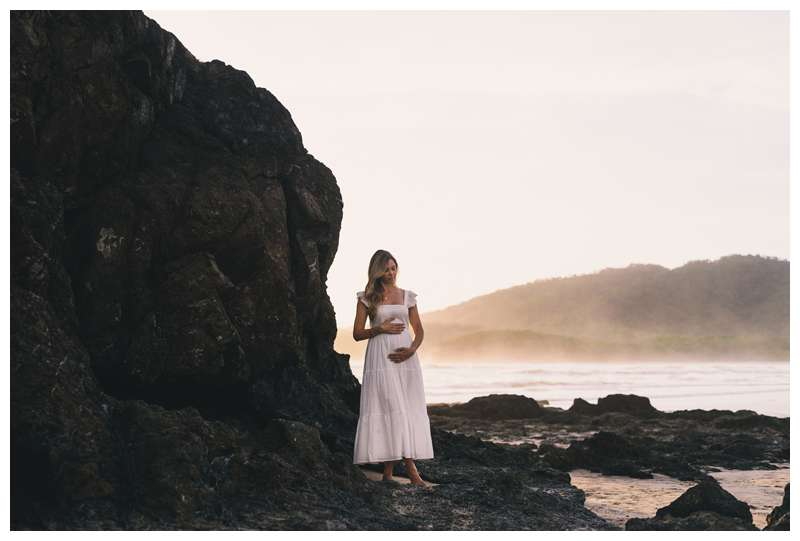Pregnant woman portrait on the beach during and low tide volcanic rocks. Beach maternity photos in Playa Grande Costa Rica.  Photographed by Kristen M. Brown of Samba to the Sea Photography.