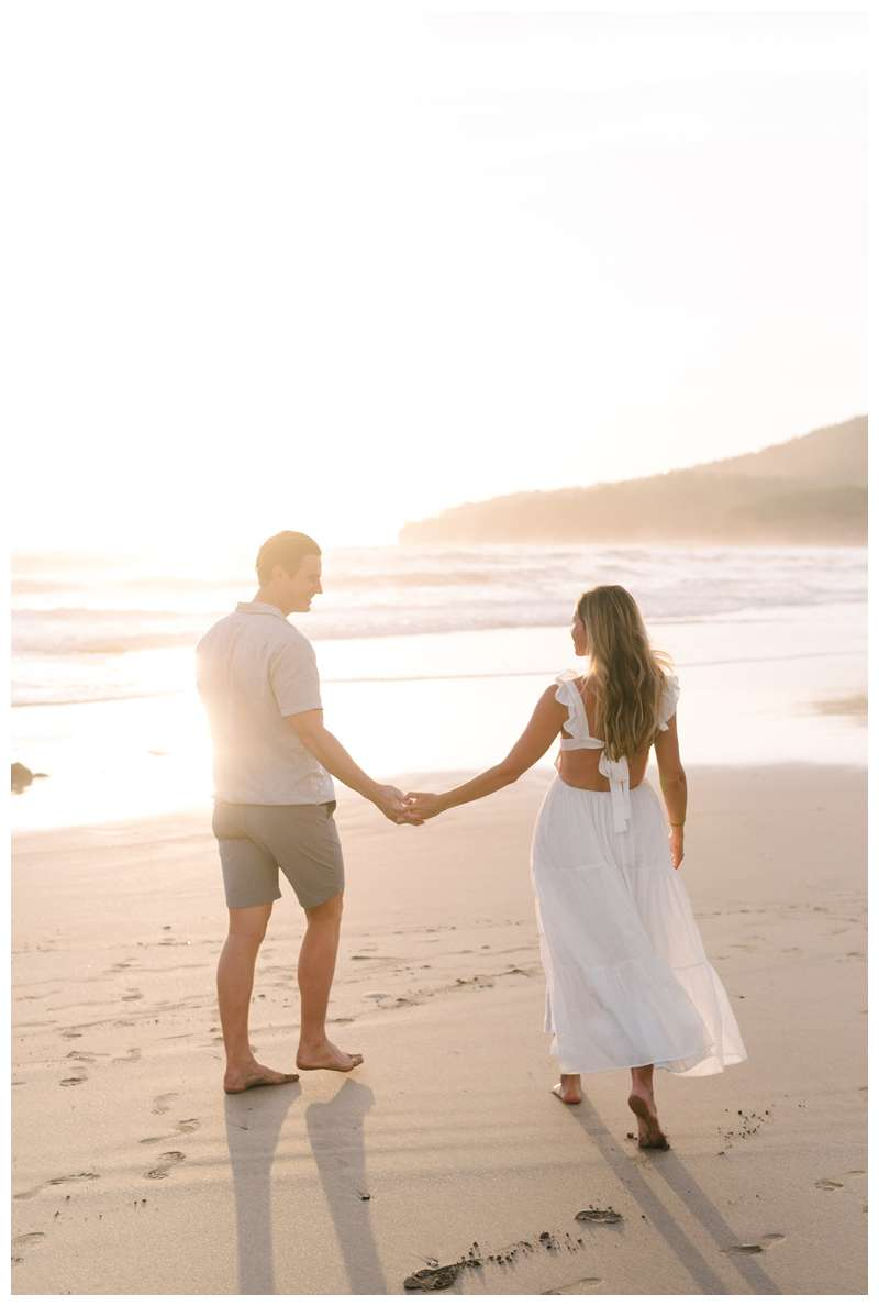 Husband and wife walking on the beach during their beach maternity photos in Playa Grande Costa Rica.  Photographed by Kristen M. Brown of Samba to the Sea Photography.