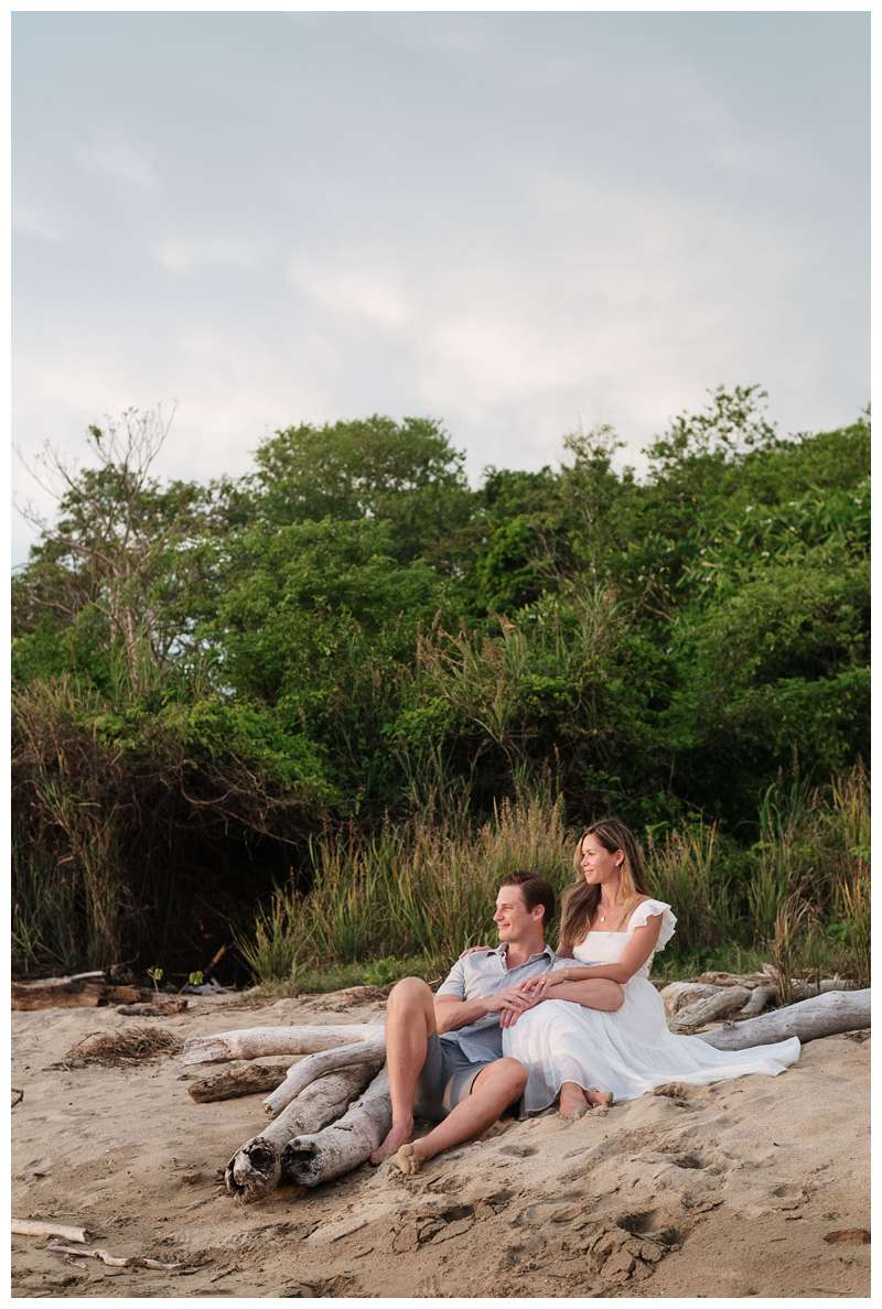 Husband and wife sitting on the beach during their beach maternity photos in Playa Grande Costa Rica.  Photographed by Kristen M. Brown of Samba to the Sea Photography.