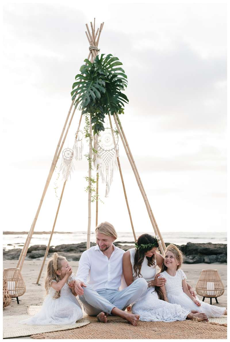Family sitting under a boho wood teepee for their vow renewal ceremony. Beach vow renewal in Tamarindo Costa Rica. Photographed by Kristen M. Brown of Samba to the Sea.