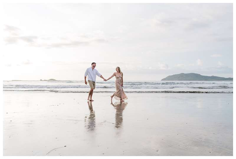 Photo of husband and wife walking on the beach. Costa Rica honeymoon photos in Tamarindo. Photographed by Kristen M. Brown of Samba to the Sea Photography.