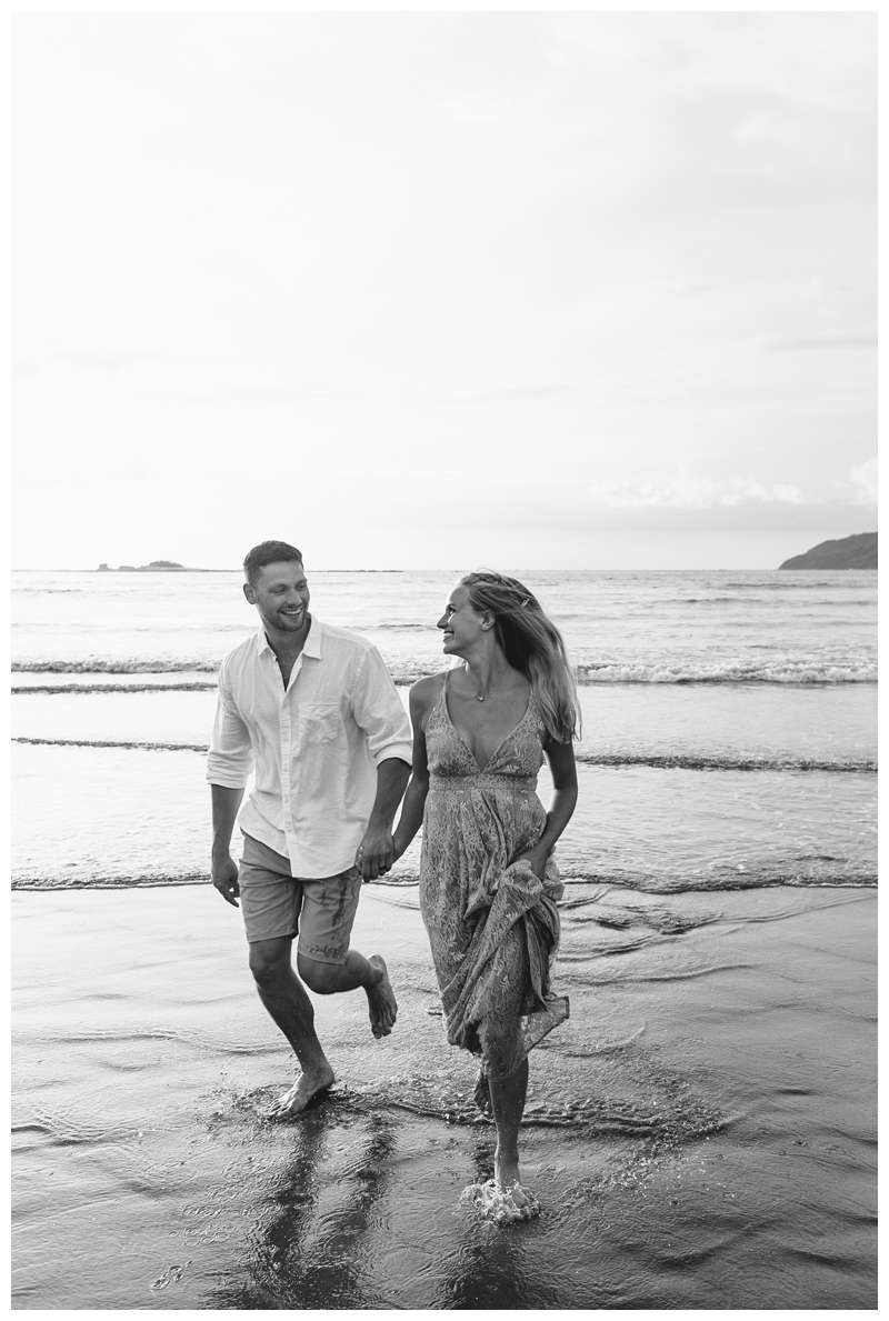 Black and white photo of husband and wife running on the beach. Costa Rica honeymoon photos in Tamarindo. Photographed by Kristen M. Brown of Samba to the Sea Photography.