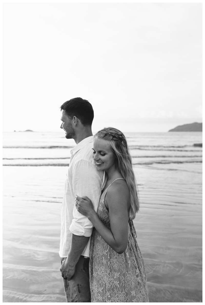 Black and white photo of husband and wife embracing on the beach. Costa Rica honeymoon photos in Tamarindo. Photographed by Kristen M. Brown of Samba to the Sea Photography.