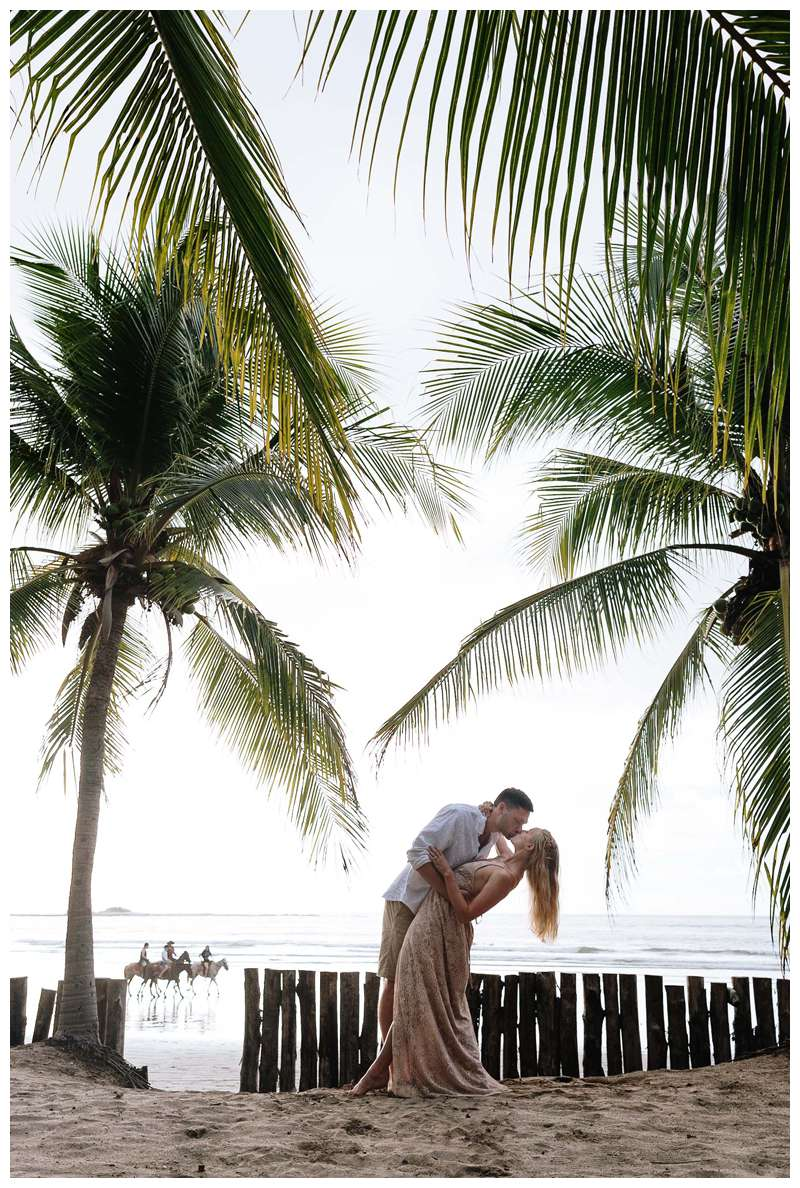 Husband and wife kissing under palm trees on the beach. Costa Rica honeymoon photos in Tamarindo. Photographed by Kristen M. Brown of Samba to the Sea Photography.