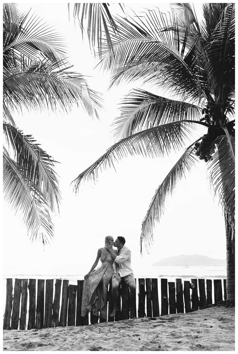 Black and white photo of husband and wife kissing under palm trees on the beach. Costa Rica honeymoon photos in Tamarindo. Photographed by Kristen M. Brown of Samba to the Sea Photography.