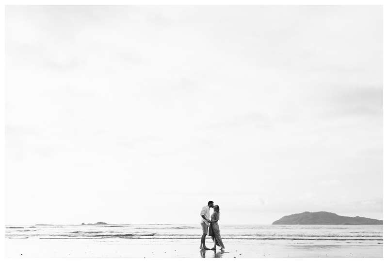 Black and white photo of husband and wife kissing on the beach. Costa Rica honeymoon photos in Tamarindo. Photographed by Kristen M. Brown of Samba to the Sea Photography.