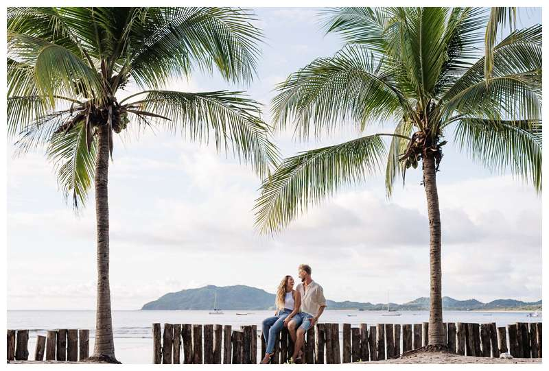 Photo of husband and wife laughing on the beach under palm trees.  Honeymoon photos on the beach in Costa Rica in Tamarindo. Photographed by Kristen M. Brown of Samba to the Sea Photography.