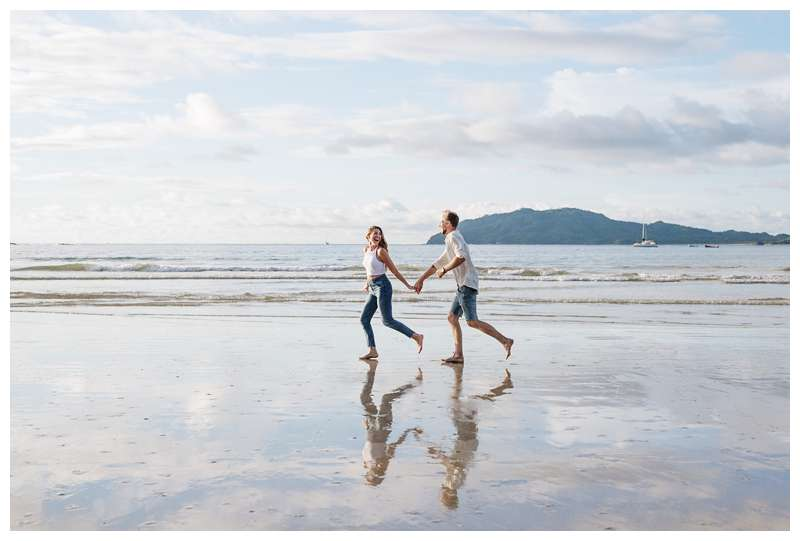Photo of husband and wife running on the beach with pretty low tide reflections on the sand.  Honeymoon photos on the beach in Costa Rica in Tamarindo. Photographed by Kristen M. Brown of Samba to the Sea Photography.