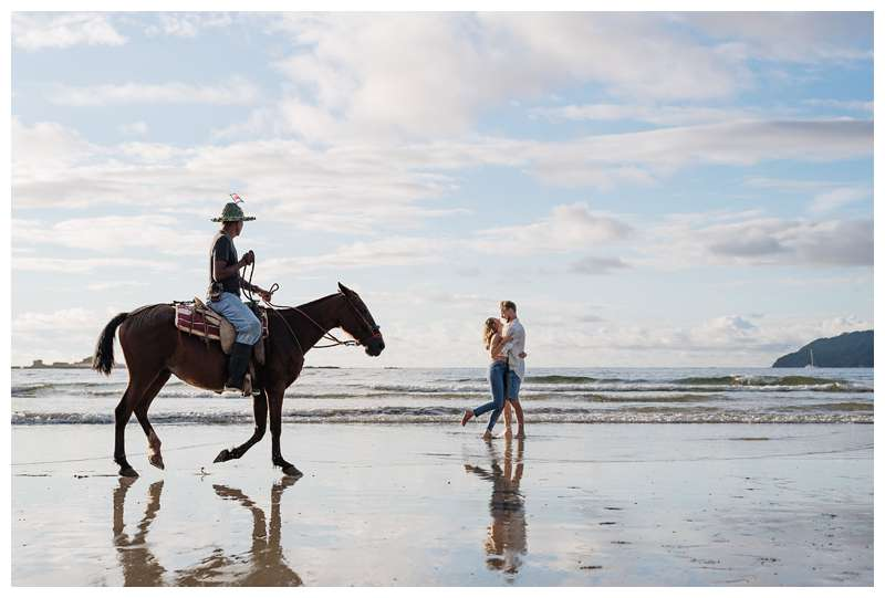 Photo of husband and wife laughing on the beach while being photo bombed by a horse.  Honeymoon photos on the beach in Costa Rica in Tamarindo. Photographed by Kristen M. Brown of Samba to the Sea Photography.