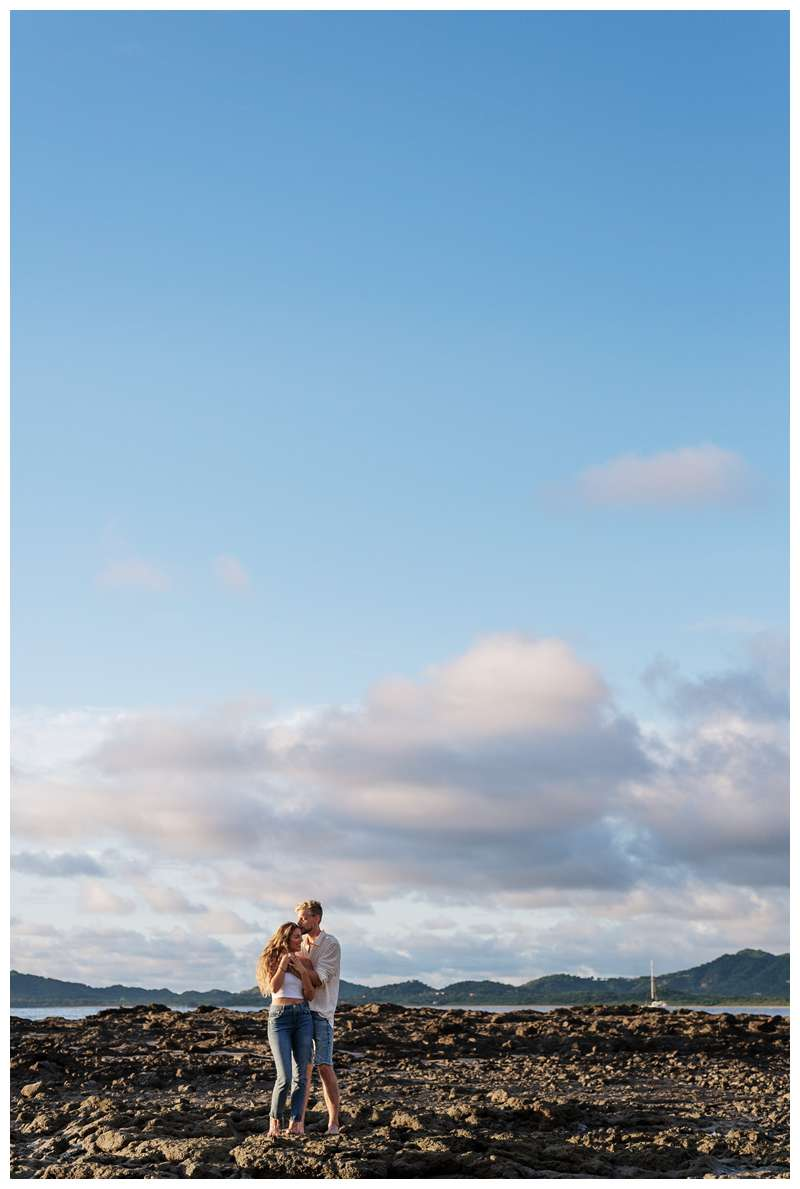 Photo of husband and wife hugging on the low tide lava rocks on the beach.  Honeymoon photos on the beach in Costa Rica in Tamarindo. Photographed by Kristen M. Brown of Samba to the Sea Photography.