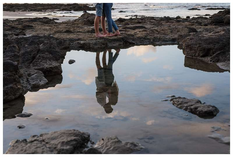Photo of husband and wife kissing on the low tide lava rocks on the beach.  Honeymoon photos on the beach in Costa Rica in Tamarindo. Photographed by Kristen M. Brown of Samba to the Sea Photography.
