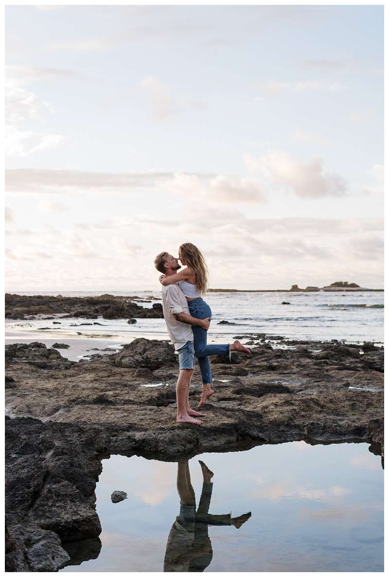 Husband holding his wife on the low tide lava rocks on the beach with a pretty low tide pool reflection.  Honeymoon photos on the beach in Costa Rica in Tamarindo. Photographed by Kristen M. Brown of Samba to the Sea Photography.