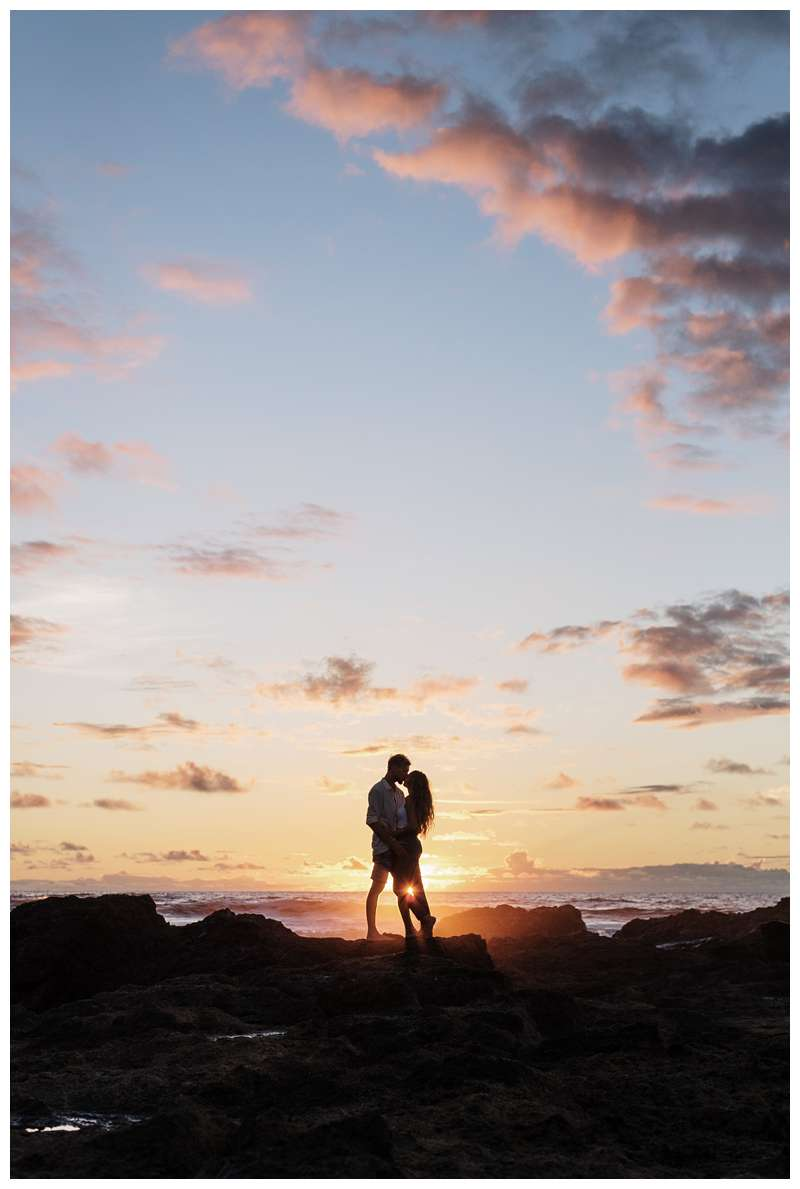 Photo of husband and wife kissing during sunset on the low tide lava rocks on the beach.  Honeymoon photos on the beach in Costa Rica in Tamarindo. Photographed by Kristen M. Brown of Samba to the Sea Photography.